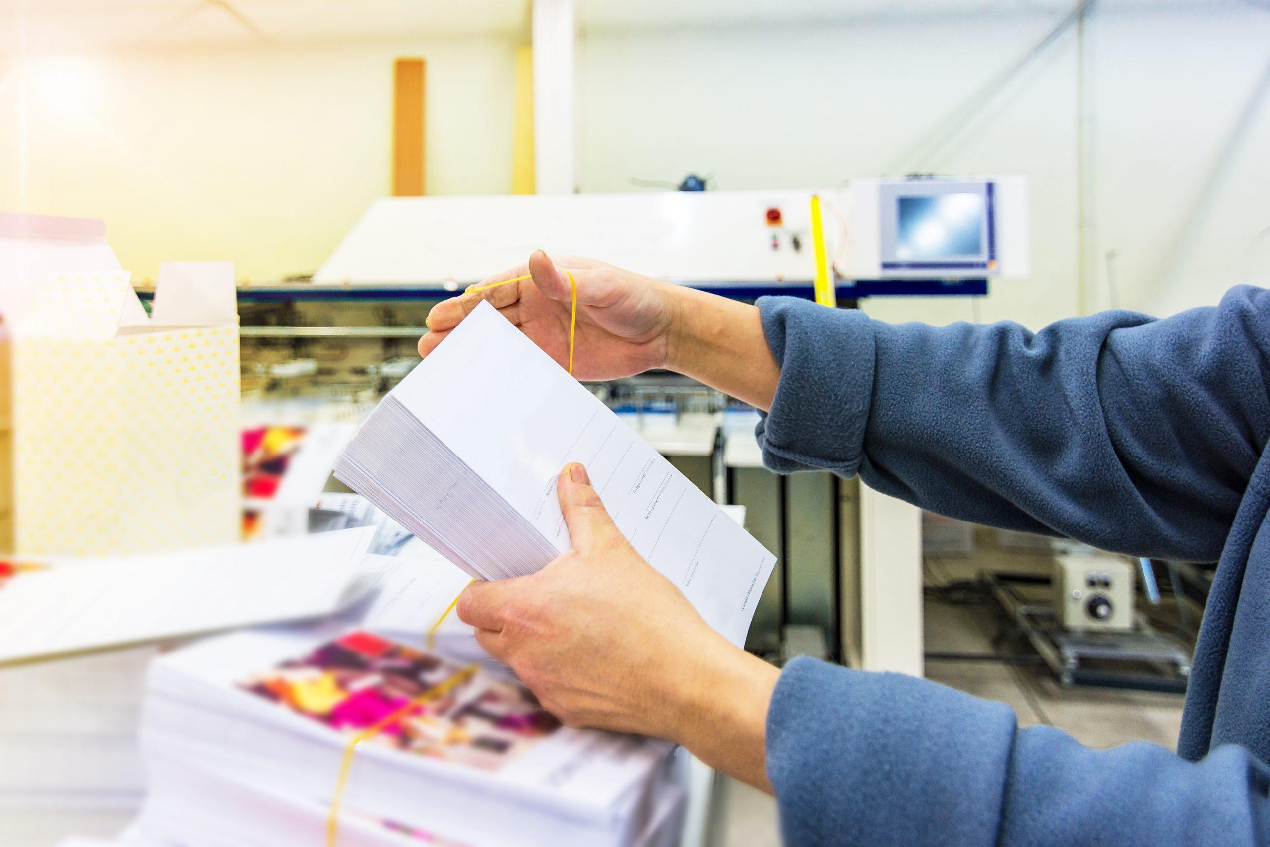 Zwei Hände verpacken einen Stapel weisser Karten für den Versand